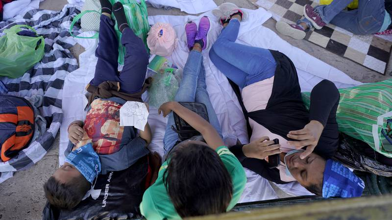 Migrants rest in a gazebo at a park after a large group of deportees were pushed by Mexican...