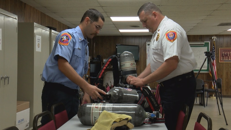 Collins Fire Department engineer Zachary Shoemake (left) and Collins Fire Chief and county fire...