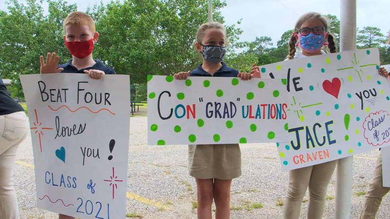 Younger students cheered the seniors on and waved posters with encouraging messages written on...