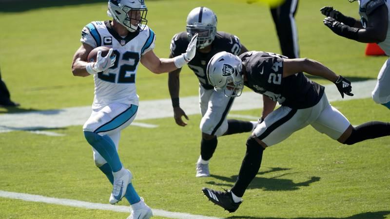 Carolina Panthers running back Christian McCaffrey scores ahead of Las Vegas Raiders safety...