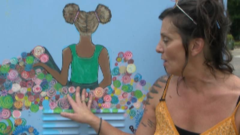 Artist Abigail Allen shows off her utility box mural downtown.
