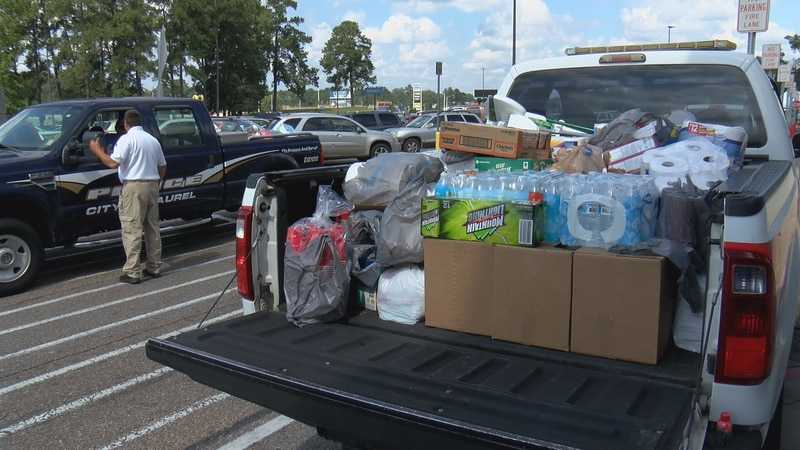 Laurel police officers and firefighters collected hurricane relief supplies at the Laurel...