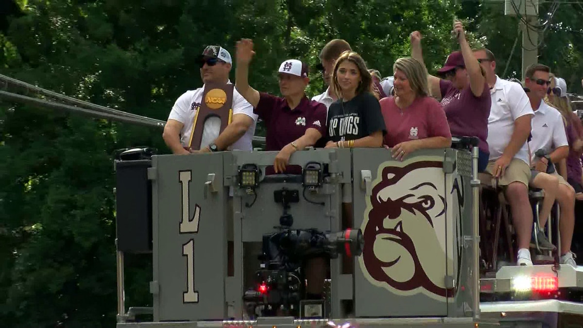 Head coach Chris Lemonis (far left) grasps the National Championship trophy at Mississippi...
