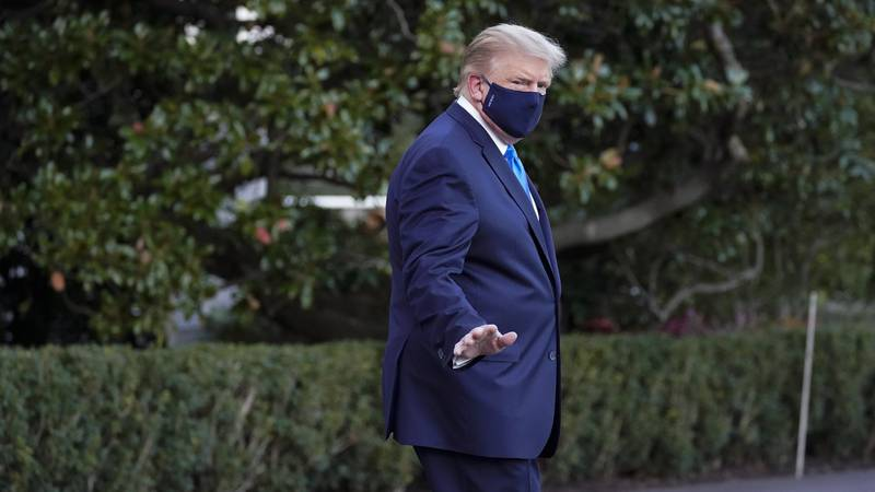 President Donald Trump waves to members of the media as he leaves the White House to go to...
