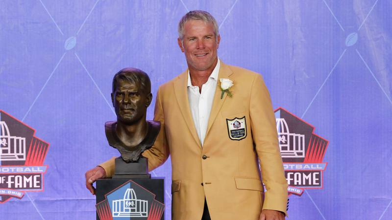 Former NFL player Brett Favre poses with a bust of himself during an induction ceremony at the...