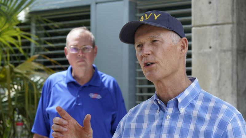 Senator Rick Scott, R-Fla., right, speaks during a news conference after having toured the...