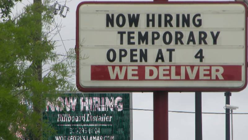 Now hiring and help wanted signs line Hardy Street in Hattiesburg.