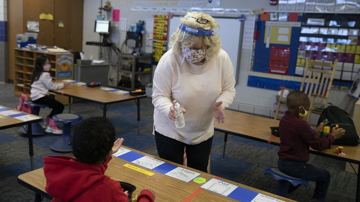 Kindergarten teacher Sherri Shober doles out hand sanitizer to students Tuesday, Jan. 19, 2021...